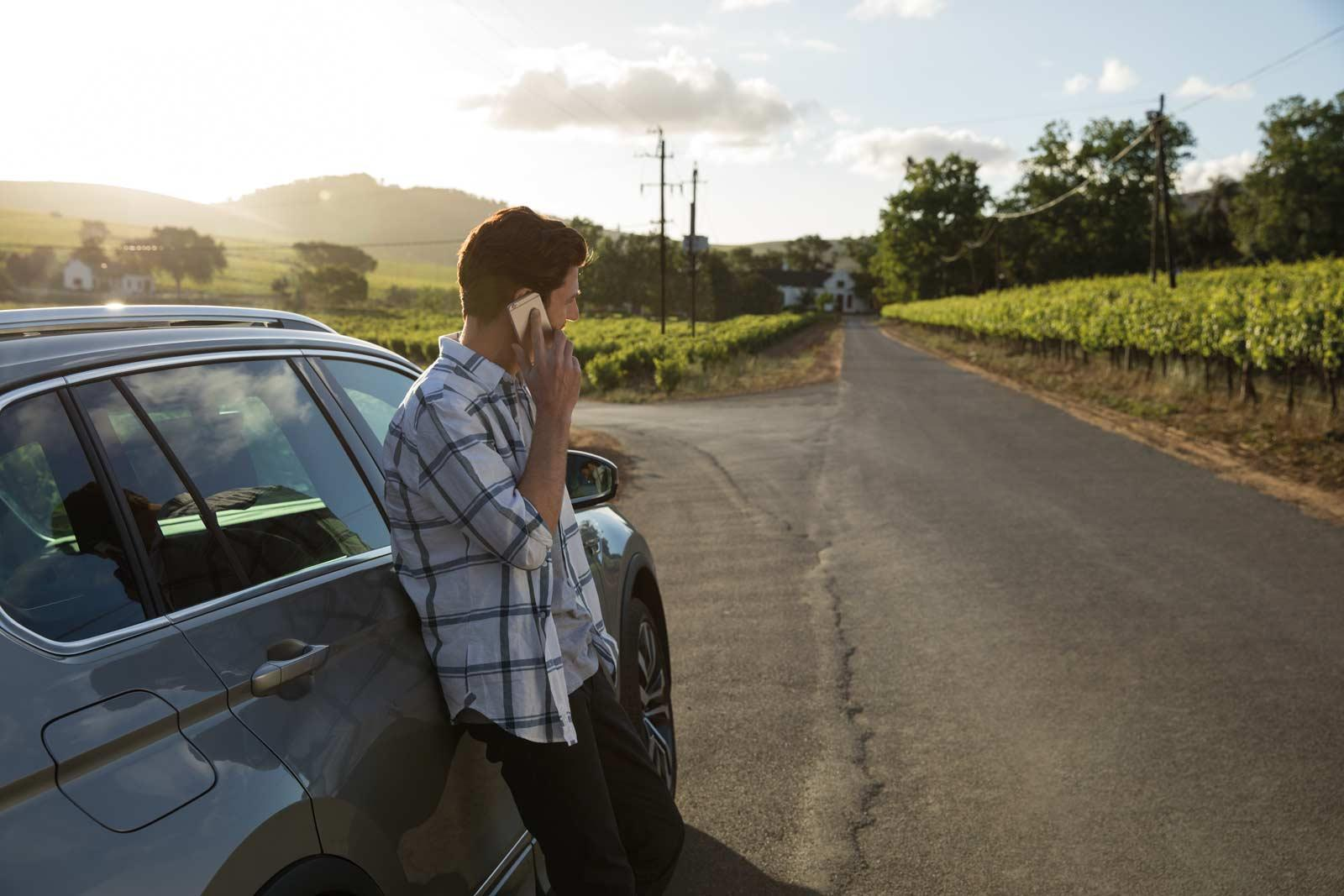 man-standing-next-to-car-with-mobile-phone