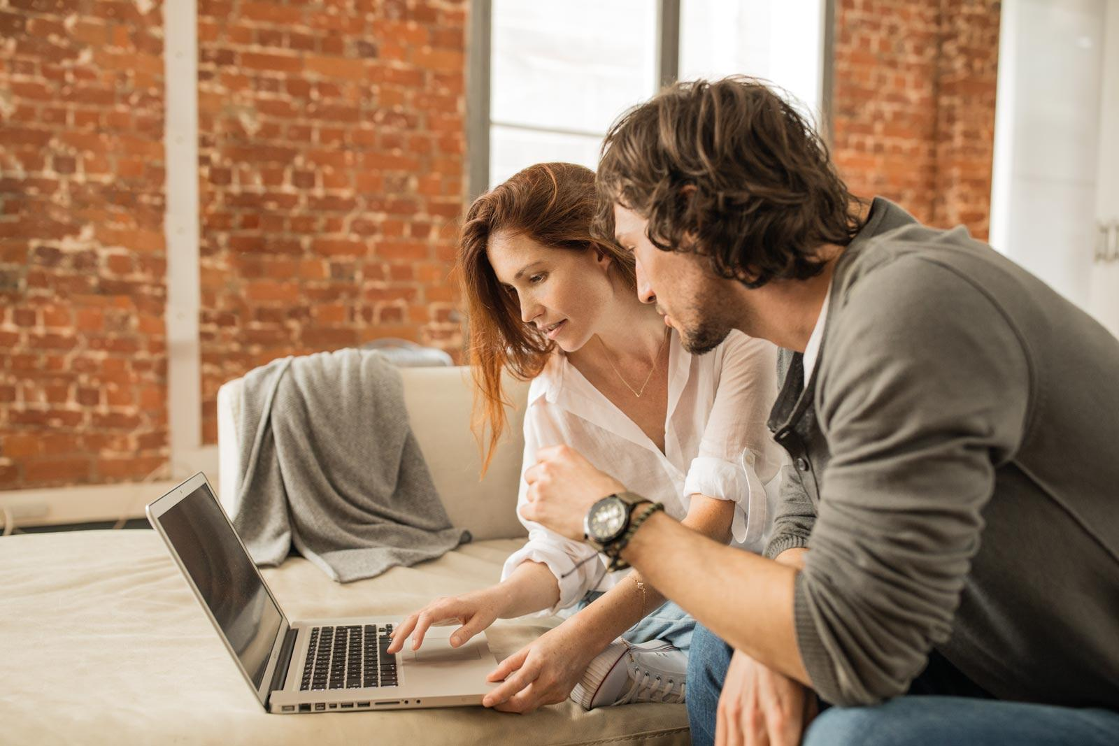 couple-sitting-in-front-of-laptop